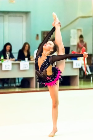 sports complex: Tyumen, Russia - April 4, 2015: All-Russian competitions in rhythmic gymnastics Spring grace. Sports complex Priboy. Young attractive girl shows own skill in exercise with maces in front of judges