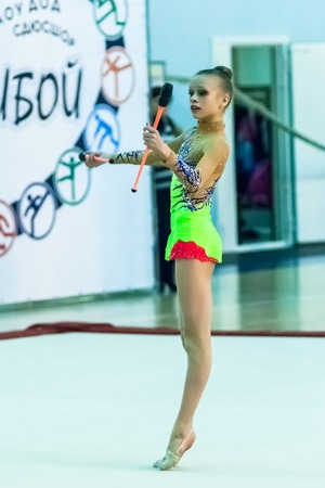 Tyumen, Russia - April 4, 2015: All-Russian competitions in rhythmic gymnastics Spring grace. Sports complex Priboy. Young beautiful girl shows own skill in exercise with maces