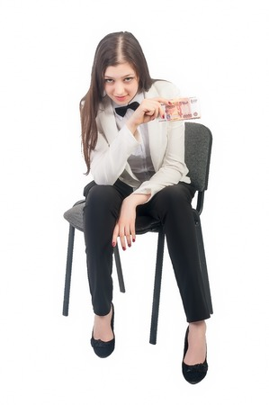roubles: Attractive business lady holds roubles, smiles and sits on old chair Stock Photo