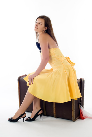 Young pretty woman sits on old suitcase over white background photo