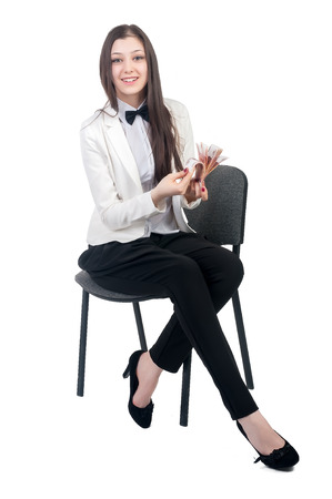 roubles: Attractive business woman holds roubles, smiles and sits on old chair Stock Photo