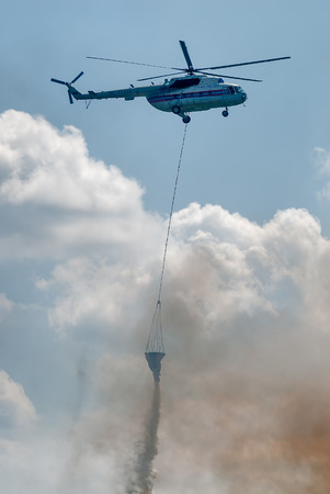 drain fly: Nizhniy Tagil, Russia - July 12. 2008: MI-8 helicopter of Emergency situations Ministry flies with water tank for fire extinguishing