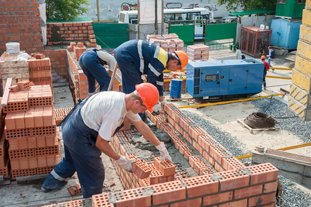 Tyumen, Russia - July 31, 2013: JSC Mostostroy-11. Construction of a 18-storeyed brick residental house at the intersection of streets of Nemtsov and Tsiolkovsky. Team of bricklayers behind work Redakční
