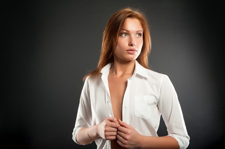 Portrait of attractive young woman at black background