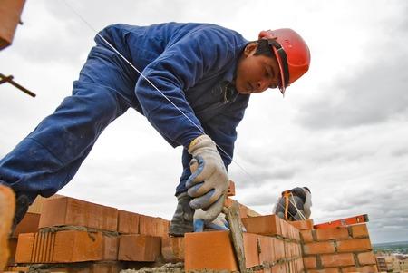 hombre con sombrero: Tyumen, Rusia - 23 de mayo de 2008: Construcci�n de 18 pisos de ladrillo casa residencial en la intersecci�n de las calles de Gercena y Chelyuskincev. Alba�il detr�s del trabajo. Se demoli� a causa del mal de base