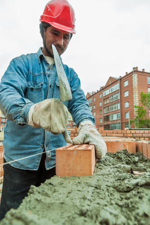 brick mason: Tyumen, Russia - May 23, 2008: 18 floor residental house at intersection of streets of Gercena and Chelyuskincev. Construction mason worker bricklayer installing red brick with trowel putty knife
