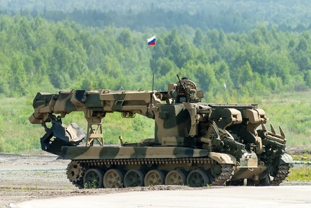 clearer: Nizhniy Tagil, Russia - July 12. 2008: Visitors explore military equipment on exhibition range. Combat engineering vehicle IMR-2MA moves