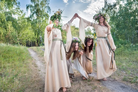 streamlet: Attractive Women with Wreath of Flowers play game streamlet in forest. Ivan Kupala Holiday Celebration