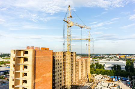 residental: Tyumen, Russia - July 16, 2015: Aerial view on lifting cranes on residental house construction site. Harkovskaya street