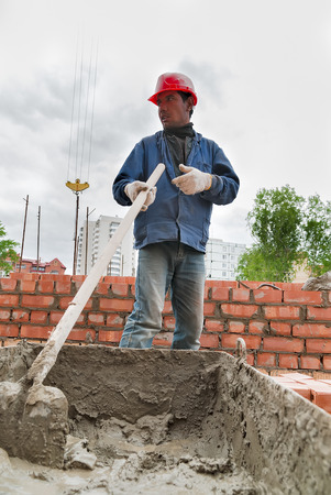 cement solution: Tyumen, Russia - May 23, 2008: Construction of 18 floor brick residental house at intersection of streets of Gercena and Chelyuskincev. Builder man working with shovel during concrete cement solution mortar preparation in mixer at construction site
