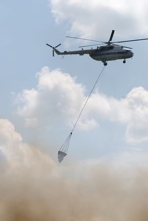 extinguishing: Nizhniy Tagil, Russia - July 12. 2008: MI-8 helicopter of Emergency situations Ministry flies with water tank for fire extinguishing