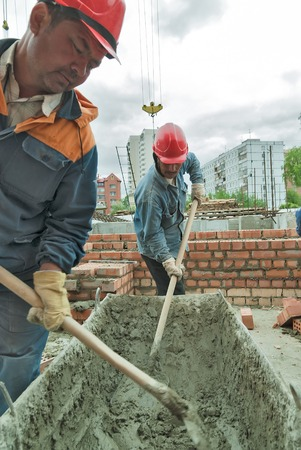 residental: Tyumen, Russia - May 23, 2008: Construction of 18 floor brick residental house at intersection of streets of Gercena and Chelyuskincev. Workers knead solution for bricklayers