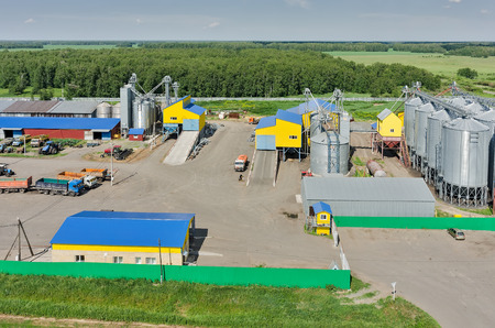 stockroom: Novikova, Russia - June 18, 2015: Aerial view onto modern machine yard of agricultural firm Russian Field. Corn dryer silos standing in machine yard. Tyumen region Stock Photo