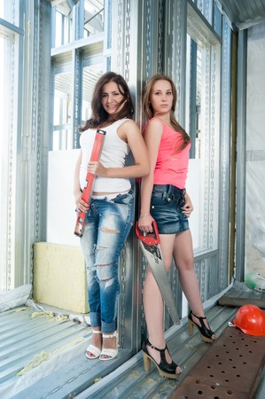 two sexy women: Two sexy women with meausering level and handsow on construction site