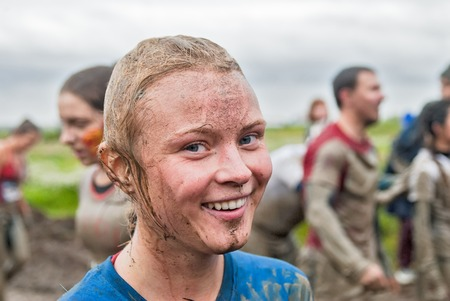 dirty girl: Tyumen, Russia - August 8, 2015: Steel Character extrim race on Krugloe lake. Gagarin park in Cape district. Obstacle stage - to get on inclined wall and to jump off in ditch with water. Happy dirty girl in action