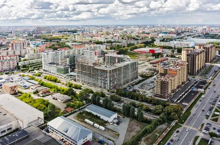 residental: Tyumen, Russia - July 16, 2015: Aerial view on lifting cranes on Novin residental house construction site. Harkovskaya street