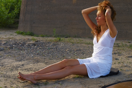 young adult woman: Young beautiful woman sitting on sand of beach Stock Photo