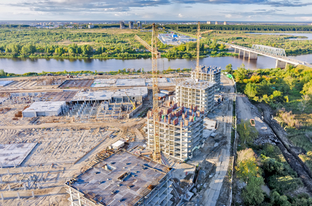 residental: Tyumen, Russia - August 27, 2015: Aerial view on lifting cranes on residental houses construction sitenear Tura river. Combined automobile and pedestrian bridge