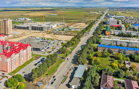 housing lot: Tyumen, Russia - August 27, 2015: Aerial view onto Star City Mall construction and residential district on Cape. Road to Tobolsk