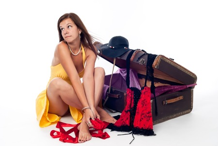 Sad pretty girl seated next to suitcase over white background photo