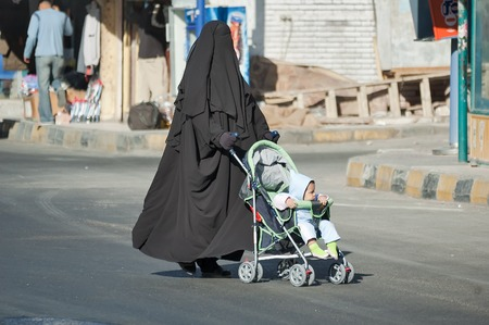 burqa: Hurghada, Egypt - November 7. 2006: Arabic mother in burqa conducts carriage with child Editorial