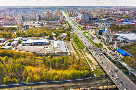 travel industry: Tyumen, Russia - May 14, 2015: Aerial view on city quarters. Melnikayte and 30 let Pobedy streets intersection, industral area, bridge over railways. Autumn season Editorial
