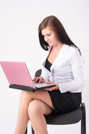 fille sexy: Jeune femme d'affaires assis sur sa chaise avec un ordinateur portable sur fond blanc Banque d'images