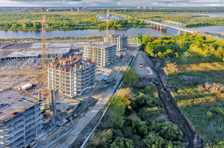 residental: Tyumen, Russia - August 27, 2015: Aerial view on lifting cranes on residental houses construction site. Combined automobile and pedestrian bridge through Tura River Editorial
