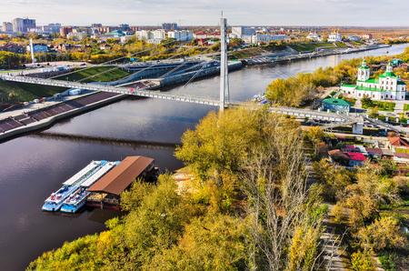 passenger ships: Tyumen, Russia - September 24, 2015: Aerial view onto pesestrian Lovers Bridge, Voznesensko-Georgiyevsky church and passenger ships during autumn period Editorial