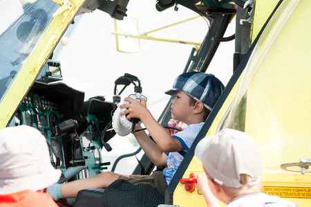 heliport: Tyumen, Russia - August 11, 2012: Air show On a visit at UTair in heliport Plehanovo. Little boy sitting in cabin of the MI-8 helicopter