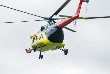 rescuer: Tyumen, Russia - August 23, 2008: On visit at UTair airshow in Plehanovo heliport. Rescuer is landed from MI-8 helicopter by rope Editorial
