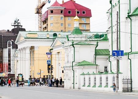 pioneers: Tyumen, Russia - May 9, 2010: People cross Chelyuskintsev Street against Church of Saviour and house of pioneers Editorial