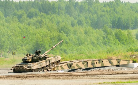 induced: Nizhniy Tagil, Russia - July 12. 2008:  T-80 tank drives on bridge induced through obstacle. Display of military equipment of land forces. RAE exhibition
