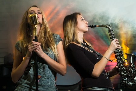 concert: Attractive young woman plays on saxophone and other one sing s in microphone on concert