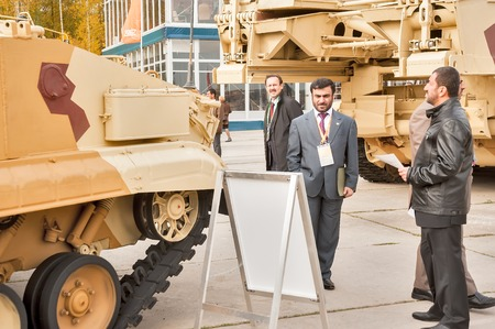 Delegation: Nizhniy Tagil, Russia - September 25. 2013: Representative of foreign delegation studies tank T-72. Modernized tank. RAE-2013 exhibition. Russian Arms Expo