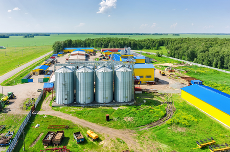 genetically modified crops: Novikova, Russia - June 18, 2015: Aerial view onto modern machine yard of agricultural firm Russian Field. Corn dryer silos standing in machine yard. Tyumen region Editorial