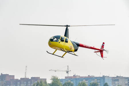heliport: Tyumen, Russia - August 11, 2012: On a visit at UTair airshow in heliport Plehanovo. Pilot of Robinson R44 Raven shows flying opportunities