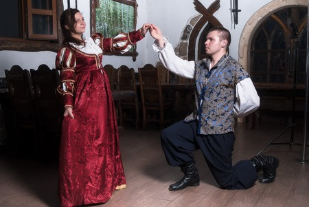 seducer: Beautiful couple woman and man in medieval clothes in the room Stock Photo