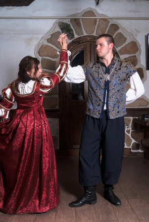 the seducer: Beautiful couple woman and man in medieval clothes in the room Stock Photo