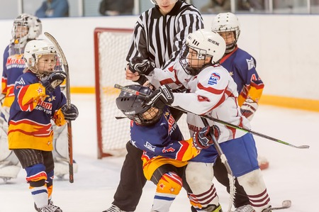 magnitogorsk: Tyumen, Russia - April 14, 2013: Hockey tournament among children teams till 9 years old. Game between Rubin 04 (Tyumen) and Metallurg 04 (Magnitogorsk). Referee separates fighting players
