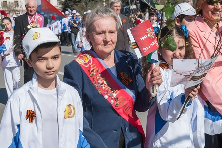 honored: Tyumen, Russia - May 9. 2009: Parade of Victory Day in Tyumen.  Veterans of sport, honored coaches and athletes with granddaughters walking