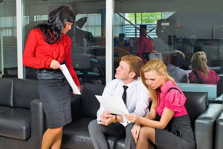 communicates: Young pretty pair communicates with manager in automobile shop Stock Photo