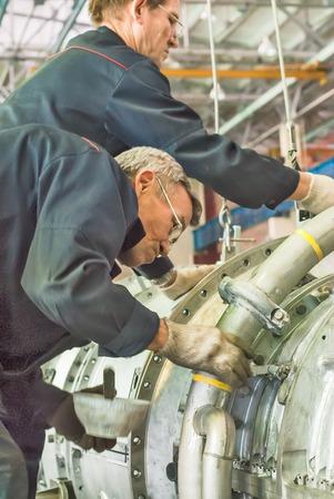 aviation: Tyumen, Russia - November 14, 2007: JSC Tyumenskie Motorostroiteli. Plant on production and repair of aviation engines. Workers install aviation engine