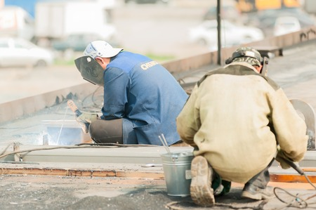 skilled labour: Tyumen, Russia - July 31, 2013: JSC Mostostroy-11. Bridge construction for outcome of Melnikayte street and Shirotnaya streei in Tyumen. Welders in action with bright sparks Editorial