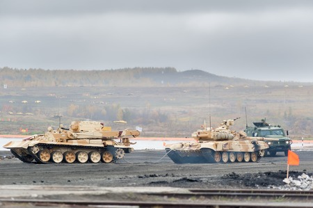 armoured: Nizhniy Tagil, Russia - September 27. 2013: Armoured recovery vehicle BREM-1M evacuates t-90S tank from battlefield on exhibition range. RAE-2013 exhibition