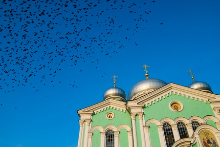 sacred trinity:  Crows fly over cathedral in glory of the Zhivonachalny and Life-giving Trinity. Sacred and Troitsk Serafimo-Diveevsky monastery Stock Photo