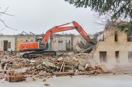 demolishing: Tyumen, Russia - December 7, 2015: Excavator demolishing barracks for new construction project. Kievskaya street 72