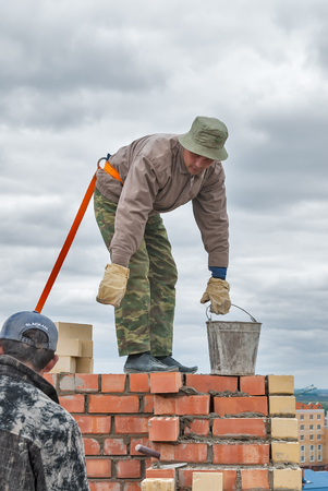 safety: Tyumen, Russia - May 23, 2008: Construction of 18 floor brick residental house at intersection of streets of Gercena and Chelyuskincev. Bricklayer behind work. It is demolished because of bad base Editorial