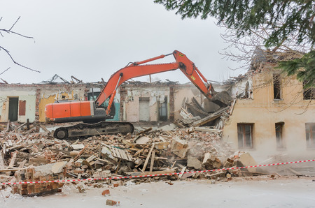 demolishing: Hydraulic crusher excavator backoe machinery working on site demolition
