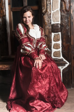 medieval: Medieval style portrait of attractive woman in red dress with wine glass in her hands Stock Photo